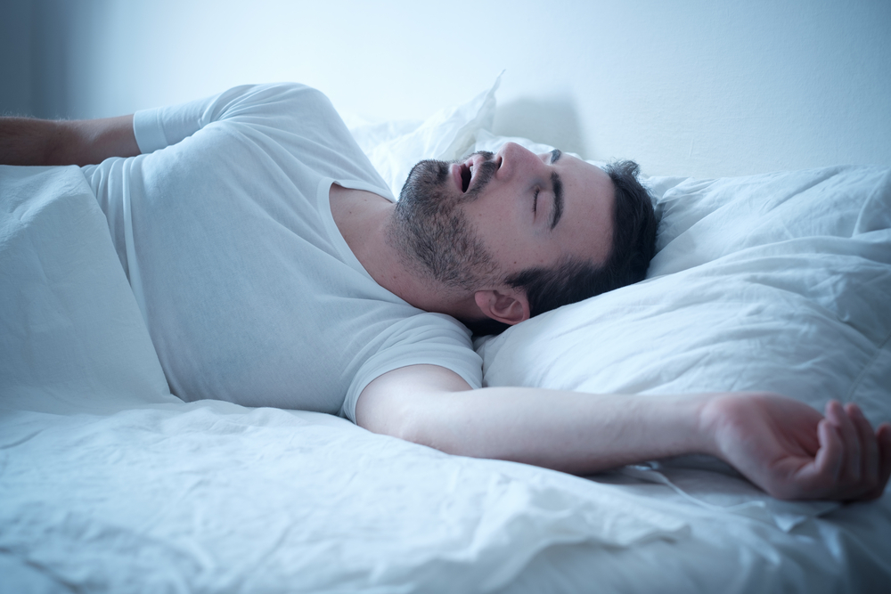 man snoring with mouth open in bed